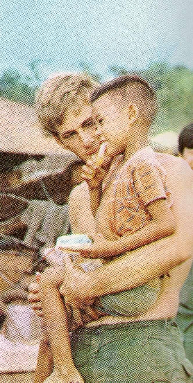 Unknown soldier holding a Vietnamese child